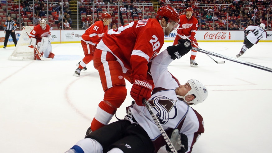 Colorado Avalanche center Ryan O'Reilly is put on the ice by Detroit Red Wings defenseman Carlo Colaiacovo (28) in the third period of an NHL hockey game Monday, April 1, 2013, in Detroit. The Red Wings defeated the Avalanche 3-2. (AP Photo/Duane Burleson)