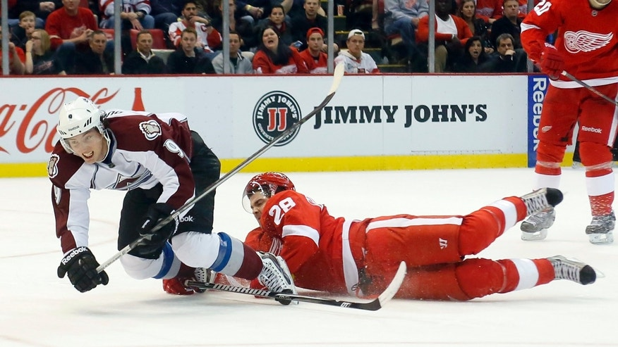 Detroit Red Wings defenseman Carlo Colaiacovo (28) uses his stick to trip Colorado Avalanche center Matt Duchene (9) in the third period of an NHL hockey game Monday, April 1, 2013, in Detroit. The Red Wings defeated the Avalanche 3-2. (AP Photo/Duane Burleson)