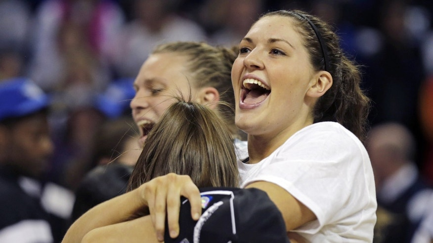 CORRECTS TO STEFANIE DOLSON- Connecticut forward Breanna Stewart smiles as she embraces teammate Stefanie Dolson after beating Kentucky in the women's NCAA regional final basketball game in Bridgeport, Conn., Monday, April 1, 2013. Connecticut won 83-53 and advances to the Final Four. (AP Photo/Charles Krupa)