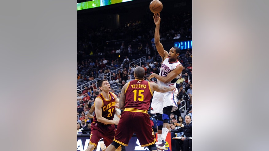 Atlanta Hawks center Al Horford (15) passes the ball under pressure from Cleveland Cavaliers' Chris Quinn (20) and Marreese Speights (15)in the first half of an NBA basketball game at Philips Arena in Atlanta, on Monday, April 1, 2013. (AP Photo/David Tulis)