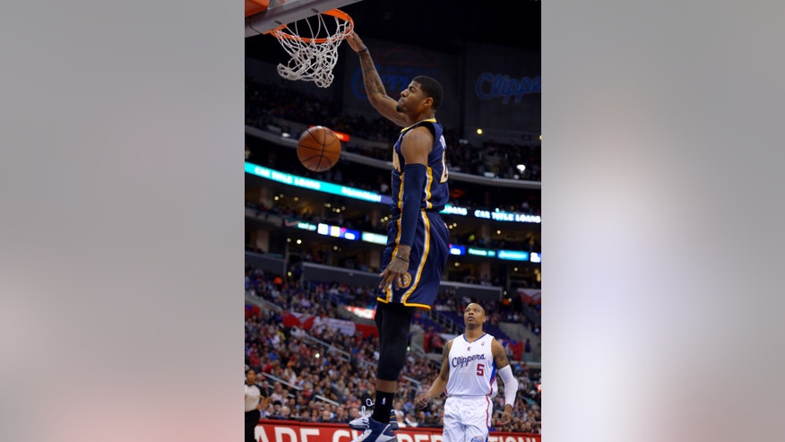 Indiana Pacers forward Paul George, left, dunks as Los Angeles Clippers forward Caron Butler watches during the first half of their NBA basketball game, Monday, April 1, 2013, in Los Angeles. (AP Photo/Mark J. Terrill)