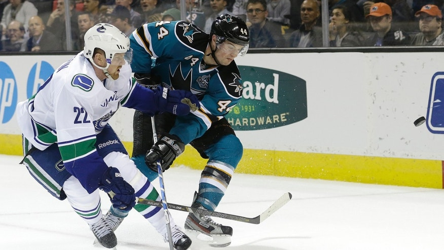 Vancouver Canucks left wing Daniel Sedin (22), from Sweden, and San Jose Sharks defenseman Marc-Edouard Vlasic (44) fight for the puck during the second period of an NHL hockey game in San Jose, Calif., Monday, April 1, 2013. (AP Photo/Jeff Chiu)