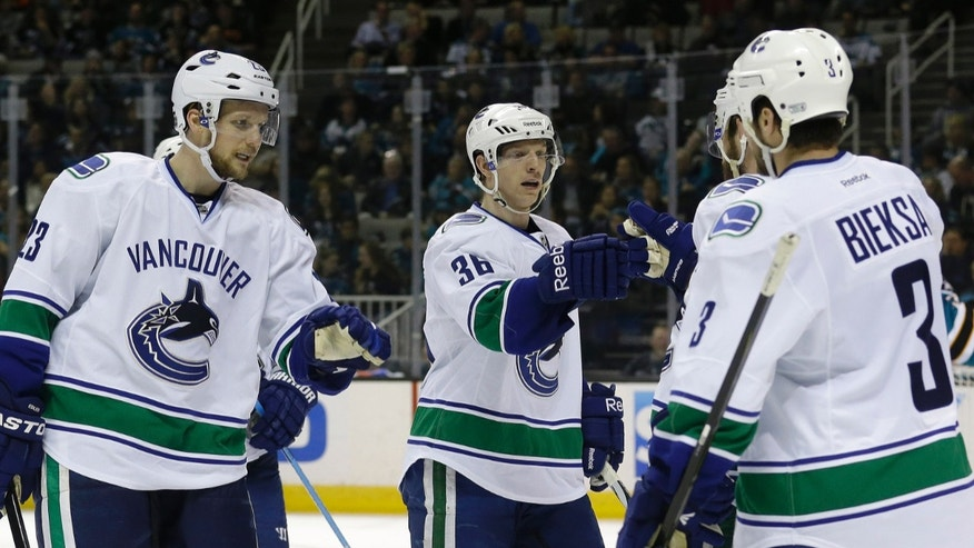 Vancouver Canucks defenseman Alexander Edler (23), from Sweden, right wing Jannik Hansen (36), from Denmark, and defenseman Kevin Bieksa (3) congratulate left wing Chris Higgins, hidden, after scoring during the second period of an NHL hockey game against the San Jose Sharks in San Jose, Calif., Monday, April 1, 2013. (AP Photo/Jeff Chiu)