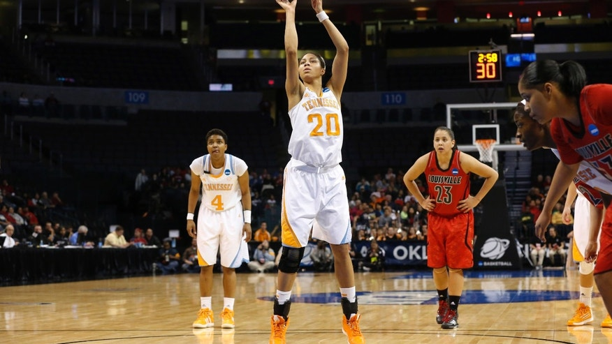 Tennessee center Isabelle Harrison (20) shoots a foul shot in front of guard Kamiko Williams (4) and Louisville guard Shoni Schimmel (23) during the first half of the regional final in the NCAA women's college basketball tournament in Oklahoma City, Tuesday, April 2, 2013. (AP Photo/Sue Ogrocki)