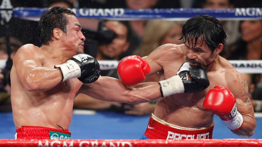 Juan Manuel Marquez, left, lands a punch against Manny Pacquiao during the fifth round during a WBO welterweight title fight,  Saturday, Nov. 12, 2011, in Las Vegas. Pacquiao won by majority decision. (AP Photo/Isaac Brekken)