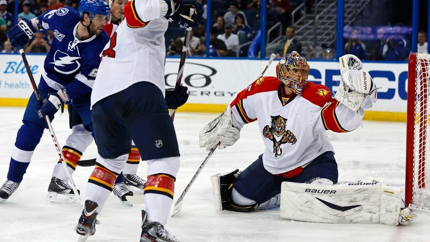 Florida Panthers goalie Jacob Markstrom, right, of Sweden, makes a save in front of Tampa Bay Lightning's Benoit Pouliot during the second period of an NHL hockey game Tuesday, April 2, 2013, in Tampa, Fla. (AP Photo/Mike Carlson)