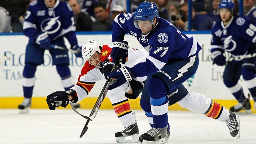 Tampa Bay Lightning defenseman Victor Hedman (77), of Sweden, tries to avoid the check of Florida Panthers' Jerred Smithson during the first period of an NHL hockey game Tuesday, April 2, 2013, in Tampa, Fla. (AP Photo/Mike Carlson)