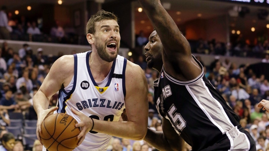 Memphis Grizzlies' Marc Gasol (33), of Spain, takes the ball around San Antonio Spurs' DeJuan Blair during the first half of an NBA basketball game in Memphis, Tenn., Monday, April 1, 2013. (AP Photo/Danny Johnston)