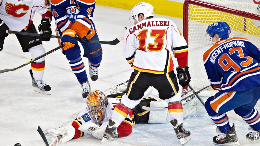 Calgary Flames goalie Joey MacDonald (35) makes the save as Mike Cammalleri (13) and Edmonton Oilers Ryan Nugent-Hopkins (93) look for the rebound during second period NHL hockey action in Edmonton, Alberta, on Monday April 1, 2013. (AP Photo/The Canadian Press, Jason Franson).