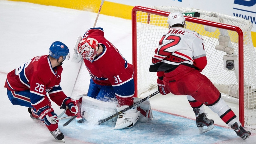 Montreal Canadiens goalie Carey Price makes a save off Carolina Hurricanes' Eric Staal as Canadiens defenseman Josh Gorges looks on during third period NHL hockey action Monday, April 1, 2013 in Montreal. The Canadiens beat the Hurricanes 4-1.  (AP Photo/The Canadian Press, Paul Chiasson)
