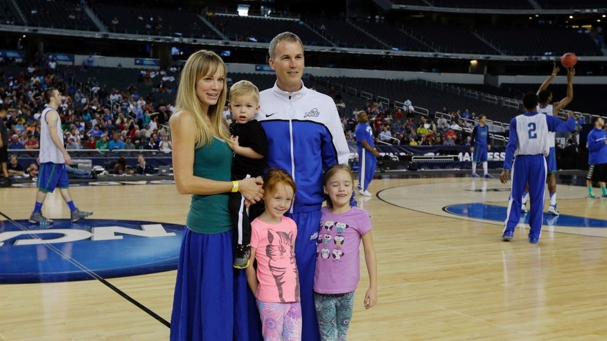 Florida Gulf Coast head coach Andy Enfield poses for a picture with his wife Amanda and kids Marcum, Aila and Lily during practice for a regional semifinal game in the NCAA college basketball tournament, Thursday, March 28, 2013, in Arlington, Texas. Florida Gulf Coast faces Florida on Friday. (AP Photo/David J. Phillip)