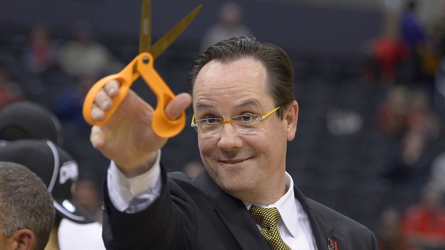 Wichita State coach Gregg Marshall holds up a pair of scissors after Wichita State defeated Ohio State 70-66 in the West Regional final in the NCAA men's college basketball tournament, Saturday, March 30, 2013, in Los Angeles. (AP Photo/Mark J. Terrill)