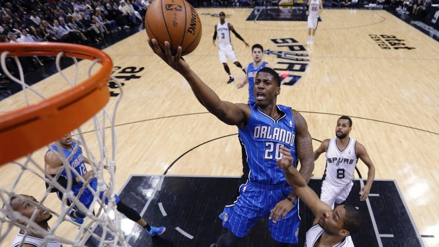 Orlando Magic's DeQuan Jones (20) shoots over San Antonio Spurs' Gary Neal, right, during the first half of an NBA basketball game, Wednesday, April 3, 2013, in San Antonio. (AP Photo/Eric Gay)