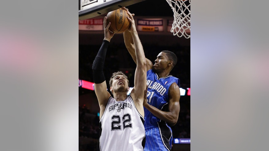 San Antonio Spurs' Tiago Splitter (22), of Brazil, is defended by Orlando Magic's Maurice Harkless (21) as he tries to shoot during the first half of an NBA basketball game, Wednesday, April 3, 2013, in San Antonio. (AP Photo/Eric Gay)