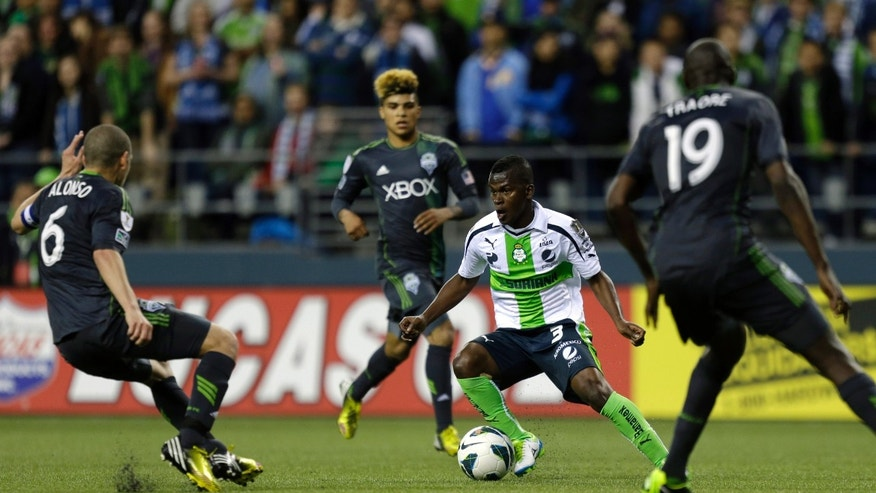 Santos Laguna's Carlos Darwin Quintero (3) squares off against Seattle Sounders' Osvaldo Alonso (6), and Djimi Traore (19) in the first half of a CONCACAF semifinal soccer match, Tuesday, April 2, 2013, in Seattle. (AP Photo/Ted S. Warren)