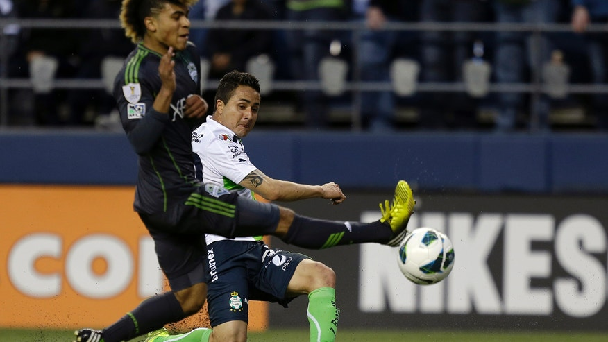Santos Laguna's Osmar Mares, right, gets a shot off past the defense of Seattle Sounders' DeAndre Yedlin, left, in the first half of a CONCACAF semifinal soccer match, Tuesday, April 2, 2013, in Seattle. (AP Photo/Ted S. Warren)