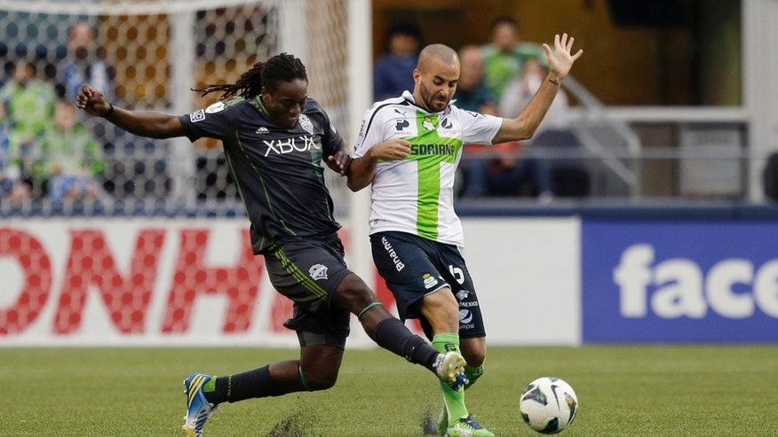 Santos Laguna's Marc Crosas, right, battles with Seattle Sounders' Shalrie Joseph, left, for the ball in the first half of a CONCACAF semifinal soccer match, Tuesday, April 2, 2013, in Seattle. (AP Photo/Ted S. Warren)