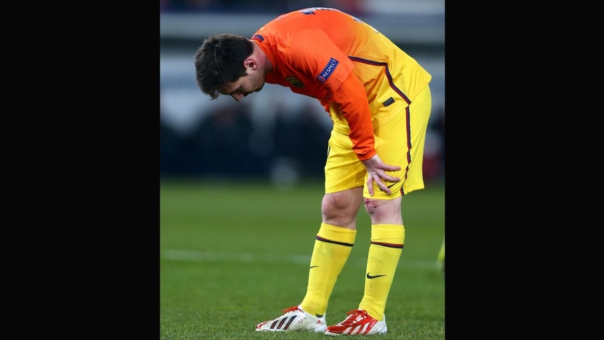 Lionel Messi of Barcelona holds his leg after pulling a muscle during the UEFA Champions League Quarter Final match against PSG on April 2, 2013 in Paris, France.  (Photo by Clive Rose/Getty Images)