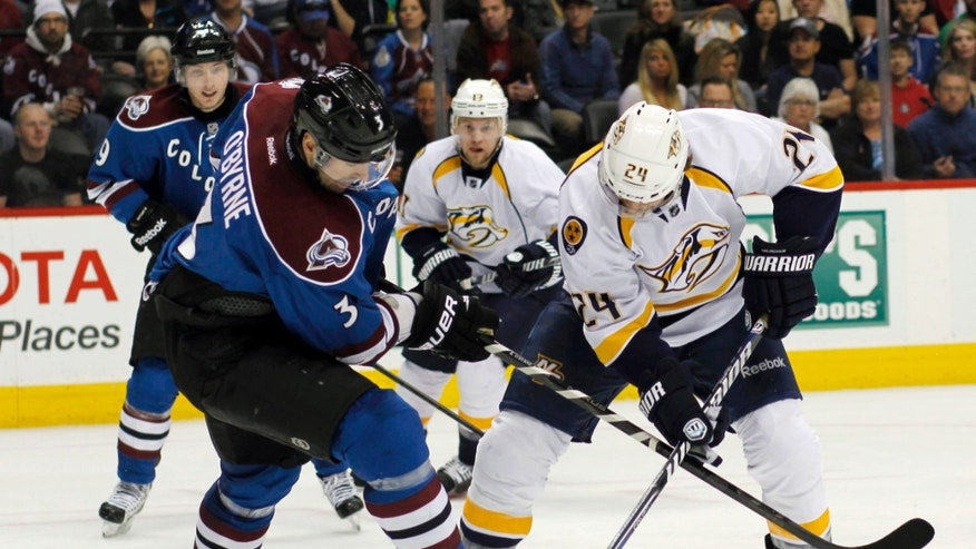 Colorado Avalanche defenseman Ryan O'Byrne, left, gets tangled up as he blocks a shot off the stick of Nashville Predators right wing Matt Halischuk in the second period of an NHL hockey game in Denver on Saturday, March 30, 2013. (AP Photo/David Zalubowski)