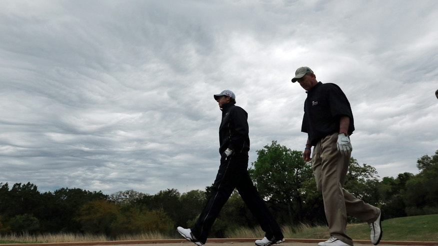 Rory McIlroy, left, of Northern Ireland, walks across  a foot bridge during the pro-am at the Texas Open golf tournament, Wednesday, April 3, 2013, in San Antonio. Play was stopped due to severe weather. (AP Photo/Eric Gay)