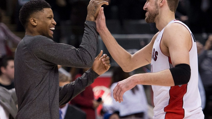 Toronto Raptors teammates Rudy Gay, left, and Jonas Valanciunas, right, react after defeating the Washington Wizards in an NBA basketball game action in Toronto, Wednesday, April 3, 2013. (AP Photo/The Canadian Press, Nathan Denette)