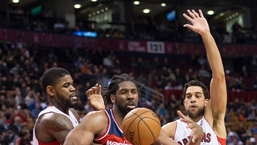 Toronto Raptors' Amir Johnson, left, and Landry Fields, right, guard Washington Wizards forward Nene, center, during second-half NBA basketball game action in Toronto, Wednesday, April 3, 2013. (AP Photo/The Canadian Press, Nathan Denette)