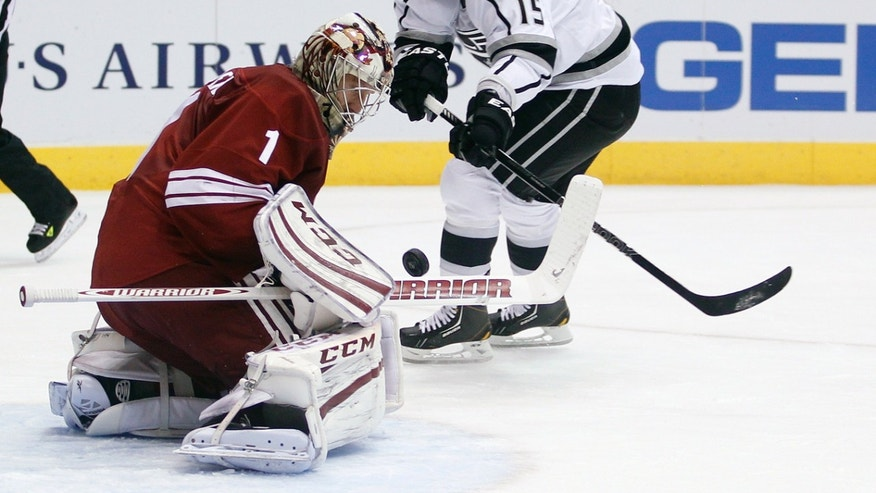 Phoenix Coyotes goalie Jason LaBarbera, left, makes a body save on a breakaway shot by Los Angeles Kings center Brad Richardson, right, in the first period of an NHL hockey game Tuesday, April 2, 2013, in Glendale, Ariz. (AP Photo/Paul Connors)