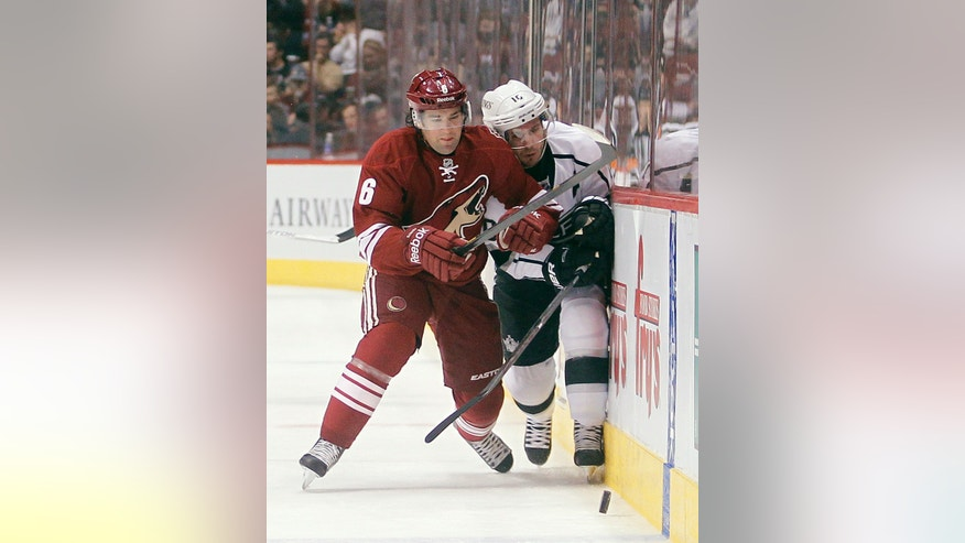 Phoenix Coyotes defenseman David Schlemko, left, checks Los Angeles Kings center Mike Richards, right, as they chase down a loose puck in the first period of an NHL hockey game Tuesday, April 2, 2013, in Glendale, Ariz. (AP Photo/Paul Connors)