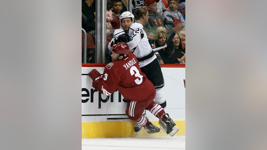 Phoenix Coyotes defenseman Keith Yandle, left, is checked by Los Angeles Kings center Jarret Stoll, right, in the first period of an NHL hockey game Tuesday, April 2, 2013, in Glendale, Ariz. (AP Photo/Paul Connors)