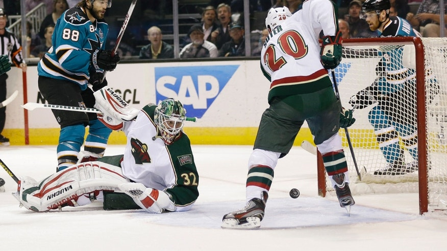 Minnesota Wild's Ryan Suter (20) clears the puck near the goal next to goalie Niklas Backstrom, center, of Finland, and San Jose Sharks' Brent Burns (88) during the first period of an NHL hockey game in San Jose, Calif., Wednesday, April 3, 2013. (AP Photo/Marcio Jose Sanchez)