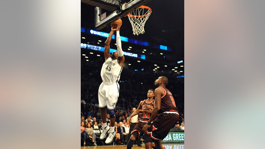 Brooklyn Nets' Gerald Wallace (45) shoots a basket in front of Chicago Bulls' Jimmy Butler (21) and Luol Deng (9) in the first half of an NBA basketball game on Thursday, April 4, 2013, at Barclays Center in New York. (AP Photo/Kathy Kmonicek)