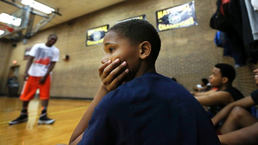 ADVANCE FOR SATURDAY, APRIL 6 - In this March 30, 2013, photo, Connor Beasley, 11, watches teams play in the Windy City Hoops program at the Kennicott Park recreation center in Chicago. Teenagers from all over Chicago's South Side have enrolled in the program and a handful of the players went to school with Hadiya Pendleton, a 15-year-old drum majorette who performed at President Barack Obama's second inauguration and was gunned down in a nearby park just two months ago.(AP Photo/Charles Rex Arbogast)