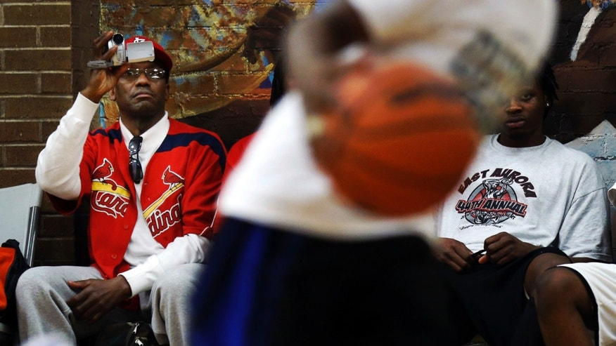 ADVANCE FOR SATURDAY, APRIL 6 - In this March 30, 2013, photo, Pierre Celestine, left, videotapes his son's performance during basketball games at the Kennicott Park recreation center, one of several sites around Chicago hosting the Windy City Hoops program for young boys and girls. (AP Photo/Charles Rex Arbogast)