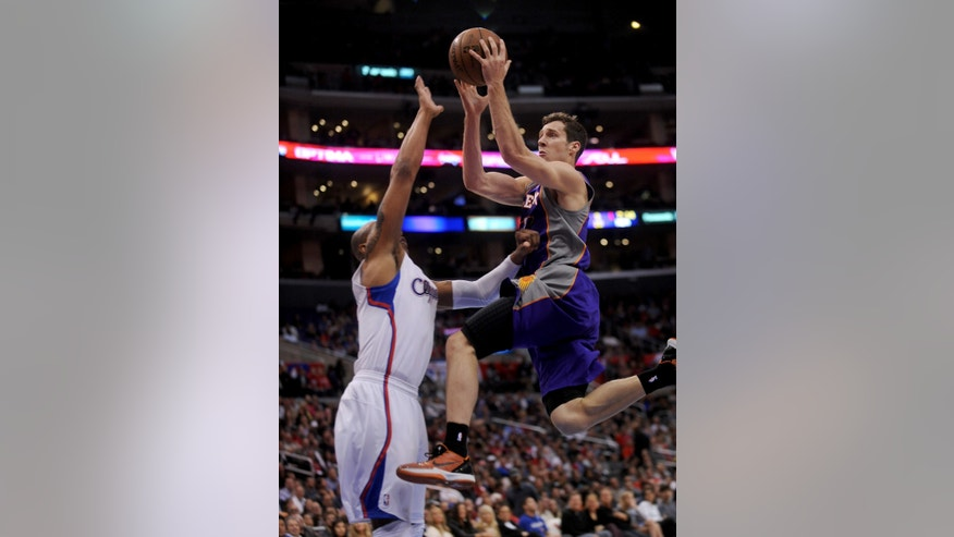 Los Angeles Clippers forward Caron Butler, left, defends as Phoenix Suns guard Goran Drapic, right, of Slovenia, drives to the basket in the first half of an NBA basketball game in Los Angeles on Wednesday, April  3, 2013. (AP Photo/Richard Hartog)