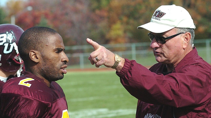 """In this Nov. 3, 2007, photo, Ed Rush, right, a football coach at Bloomsburg University, talks with receiver Brahin Bilal during practice in Bloomsburg, Pa. Rush has resigned as the Pac-12 Conference's coordinator of basketball officials following comments that he targeted Arizona coach Sean Miller during internal meetings before the conference tournament. Pac-12 Commissioner Larry Scott said in a statement released Thursday, April 4, 2013, that """"I want to express my appreciation for the great contribution Ed made to basketball officiating for the Conference during his tenure, particularly in the area of training and the cultivation of new officiating talent."""" (AP Photo/Bloomsburg Press Enterprise, Jimmy May)"""