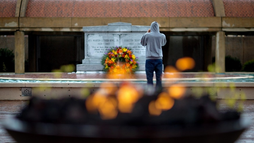 A visitor stands in front of the grave of Martin Luther King, Jr., as an eternal flame burns in the foreground on the 45th anniversary of the assassination of the civil rights leader, Thursday, April 4, 2013, in Atlanta. (AP Photo/David Goldman)