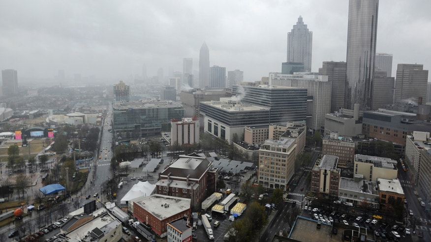Rain and clouds move through downtown, Thursday, April 4, 2013, in Atlanta. The Final Four coaches are making their first appearances in Atlanta on Thursday. The city is all dressed up for college basketball's biggest event. Stages are set up and banners have been raised in Centennial Olympic Park, near the Georgia Dome where the games will be played, but the gloomy weather put an early damper on the festive spirit. (AP Photo/Mike Stewart)