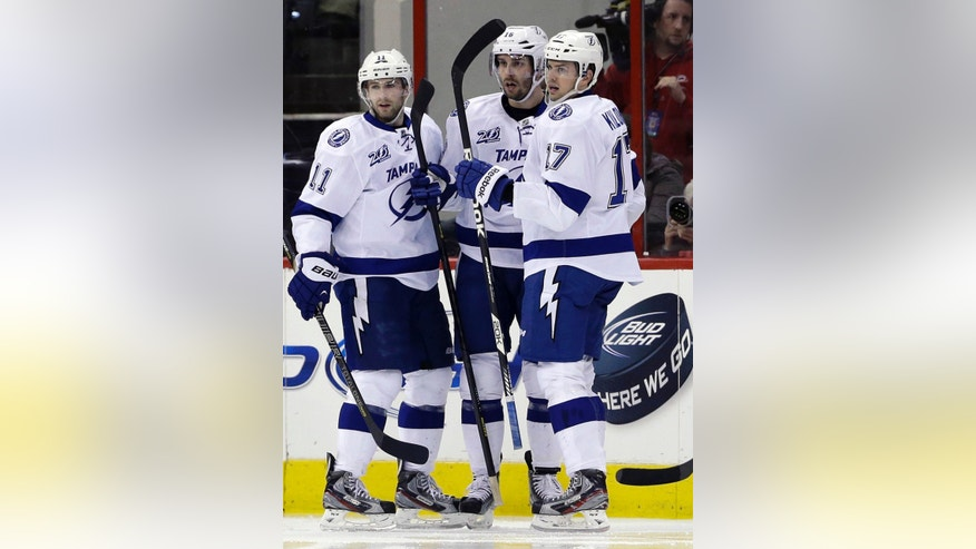 Tampa Bay Lightning's Tom Pyatt (11), Teddy Purcell and Alex Killorn (17) celebrate Purcell's goal against the Carolina Hurricanes during the second period of an NHL hockey game in Raleigh, N.C., Thursday, April 4, 2013. (AP Photo/Gerry Broome)