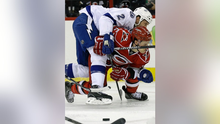 Carolina Hurricanes' Jeff Skinner (53) and Tampa Bay Lightning's Eric Brewer (2) struggle while chasing the puck during the second period of an NHL hockey game in Raleigh, N.C., Thursday, April 4, 2013. (AP Photo/Gerry Broome)