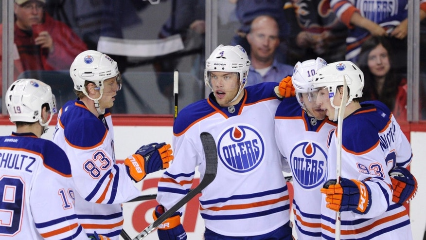 Edmonton Oilers' Taylor Hall, centre, celebrates his goal against the Calgary Flames with teammates Justin Schultz, left, Ales Hemsky, second left, from Czech Republic, Shawn Horcoff, second right, and Ryan Nugent-Hopkins during second period NHL action in Calgary, Alberta, Wednesday, April 3, 2013. (AP Photo/The Canadian Press, Larry MacDougal)