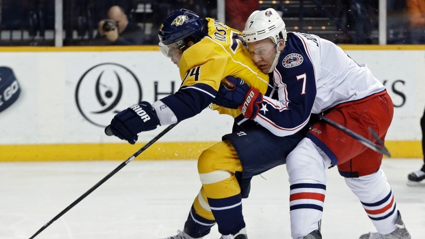 Columbus Blue Jackets defenseman Jack Johnson (7) tries to slow down Nashville Predators left wing Sergei Kostitsyn (74), of Belarus, in the second period of an NHL hockey game on Thursday, April 4, 2013, in Nashville, Tenn. (AP Photo/Mark Humphrey)