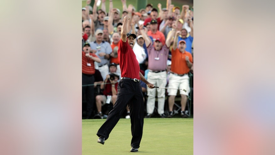 ADVANCE FOR WEEKEND EDITIONS, APRIL 6-7 - FILE - In this April 10, 2005, file photo, Tiger Woods reacts after winning the Masters in a playoff with Chris DiMarco on the 18th hole during final round play of the golf tournament at the Augusta National Golf Club in Augusta, Ga. It has been eight years since Woods rolled in a 15-foot birdie putt to win the Masters in a playoff for his fourth green jacket. (AP Photo/Elise Amendola, File)