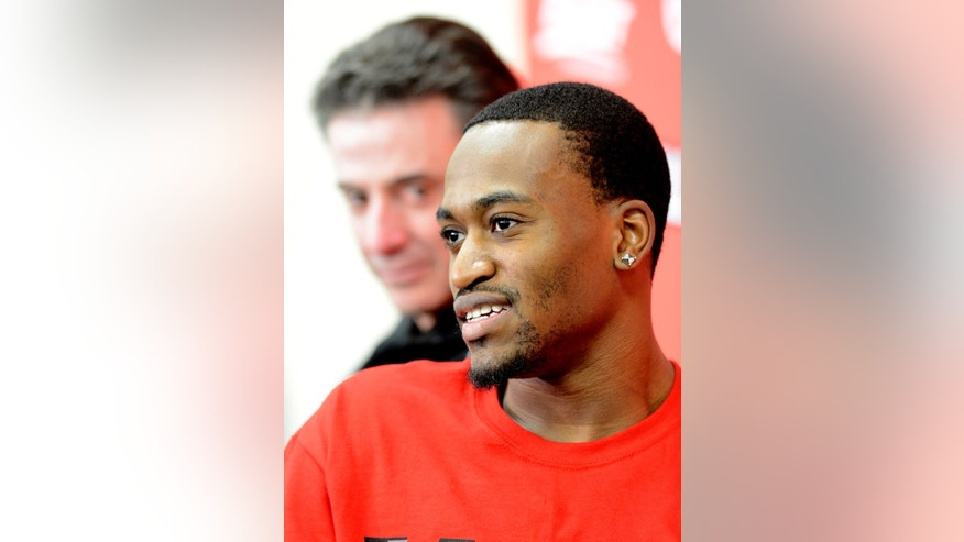 Louisville forward Kevin Ware answers questions as coach Rick Pitino looks on during a news conference, Wednesday April 3, 2013, at the KFC Yum! Center practice facility in Louisville, Ky. Ware was released from an Indianapolis hospital Tuesday, two days after millions watched him break his right leg on a horrifying play trying to block a shot during an NCAA college basketball regional championship game against Duke.  (AP Photo/Timothy D. Easley)