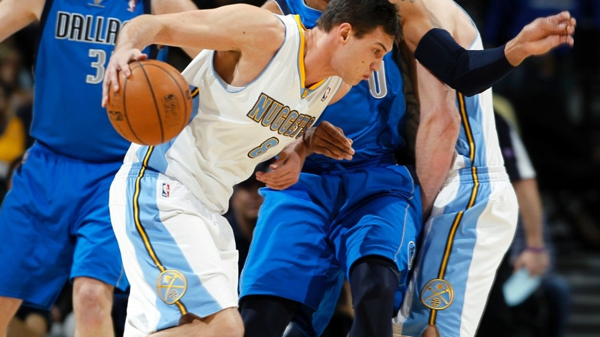 Denver Nuggets forward Danilo Gallinari, front left, of Italy, works ball inside between Dallas Mavericks center Chris Kaman, back left, and forward Shawn Marion in the first quarter of an NBA basketball game in Denver on Thursday, April 4, 2013. (AP Photo/David Zalubowski)