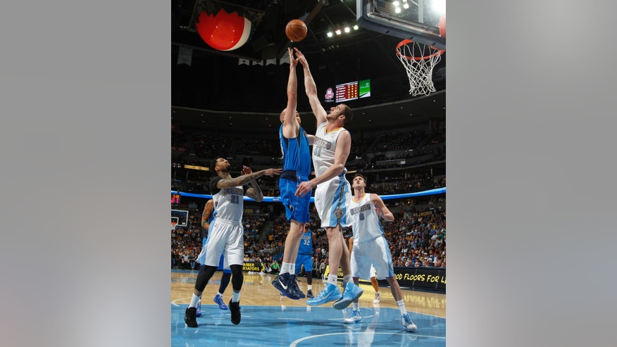 Dallas Mavericks center Chris Kaman, second from left, goes up for a shot as, from left, Denver Nuggets forward Wilson Chandler, Kosta Koufos and Danilo Gallinari, of Italy, cover in the first quarter of an NBA basketball game in Denver on Thursday, April 4, 2013. (AP Photo/David Zalubowski)