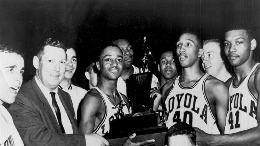 In this March 23, 1963  photo provided by Loyola University Chicago, Loyola coach George Ireland, second from left,  puts his hand on the NCAA championship trophy held by player Jerry Harkless, third from left after Loyola defeated Cincinnati in the tournament final in Louisville, Ky. At far left is player John Egan (11). And at right is Vic Rouse (40) and Les Hunter (41)  Ask college basketball fans about the game that changed the color of the sport and the answer invariably is the 1966 NCAA championship win by Texas Western over Kentucky. But every bit as important in the evolution of the game was the final 50 years ago between Loyola of Chicago and Cincinnati. (AP Photo/Courtesy of Loyola of Chicago)