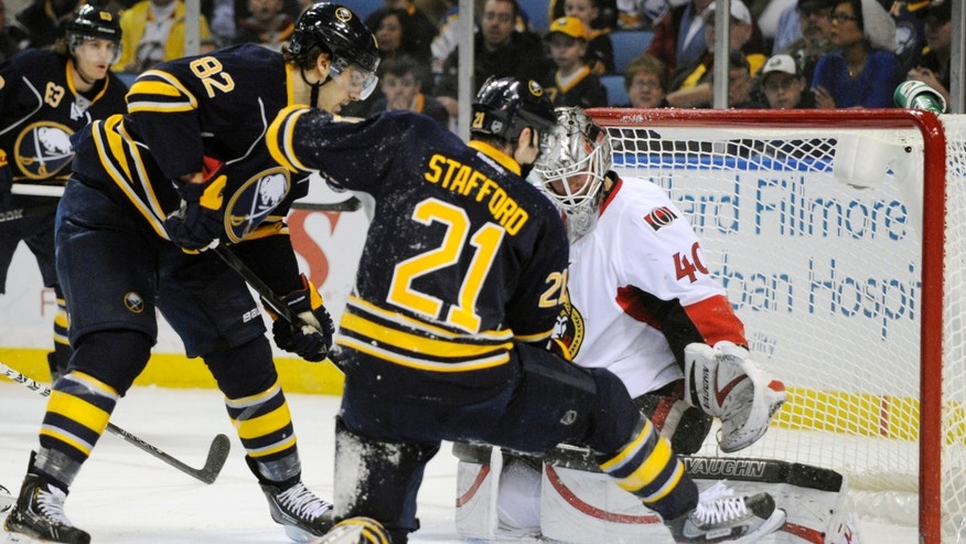 Buffalo Sabres' left winger Marcus Foligno (82) and right winger Drew Stafford (21) battle for the puck in the goal crease with Ottawa Senators'  goaltender Robin Lehner, (40), of Sweden, during the first period of an NHL hockey game in Buffalo, N.Y., Friday, April 5, 2013. (AP Photo/Gary Wiepert)
