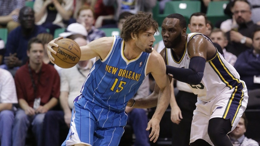 New Orleans Hornets' Robin Lopez (15) drives against Utah Jazz's Al Jefferson during the first quarter of an NBA basketball game Friday, April 5, 2013, in Salt Lake City.  (AP Photo/Rick Bowmer)