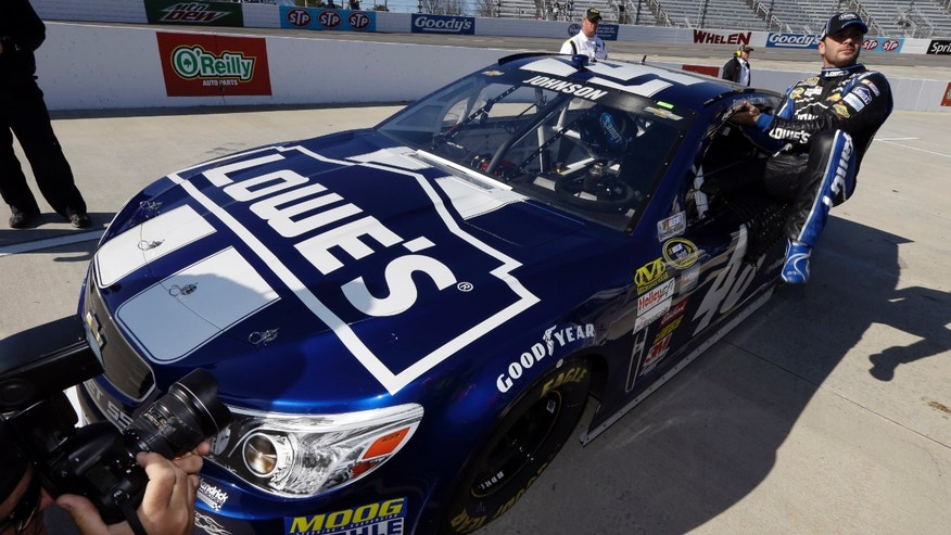 Driver Jimmie Johnson climbs out of his car during qualifying for Sunday's NASCAR Sprint Cup auto race at Martinsville Speedway in Martinsville, Va., Friday, April 5, 2013.  Johnson won the pole for the race. (AP Photo/Steve Helber)