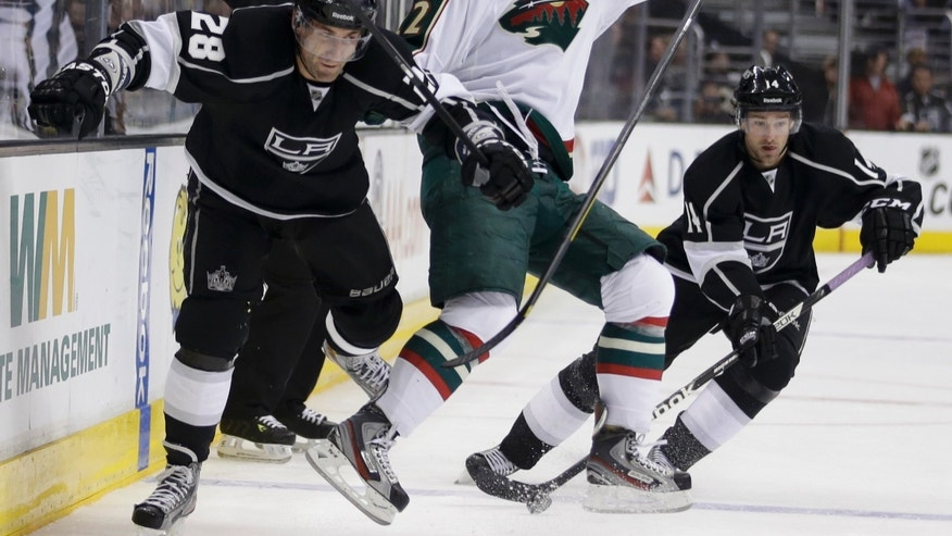 Los Angeles Kings' Jarret Stoll, left, collides with Minnesota Wild's Cal Clutterbuck as Kings' Justin Williams, background right, controls the puck during the second period of an NHL hockey game in Los Angeles, Thursday, April 4, 2013. (AP Photo/Jae C. Hong)